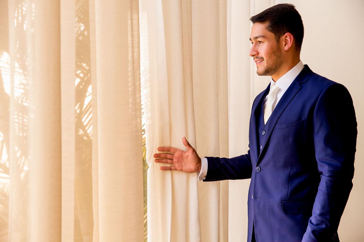 Em uma fotografia colorida, Marcos agora pronto para o grande dia, observa a paisagem pela janela.