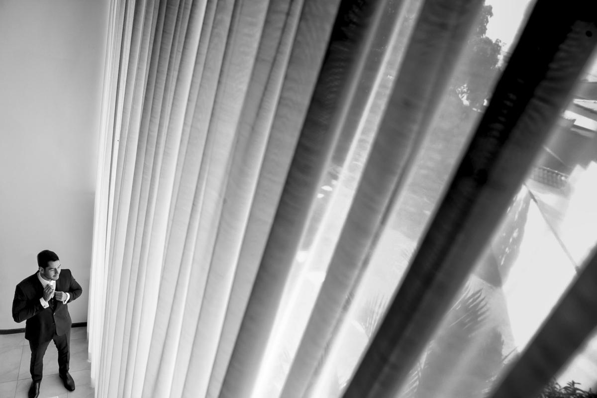 Do alto da escada o fotógrafo Sandro Andrade pega a cortina em desenhos de linhas que levam o olhar até o noivo, fotografia PB.
