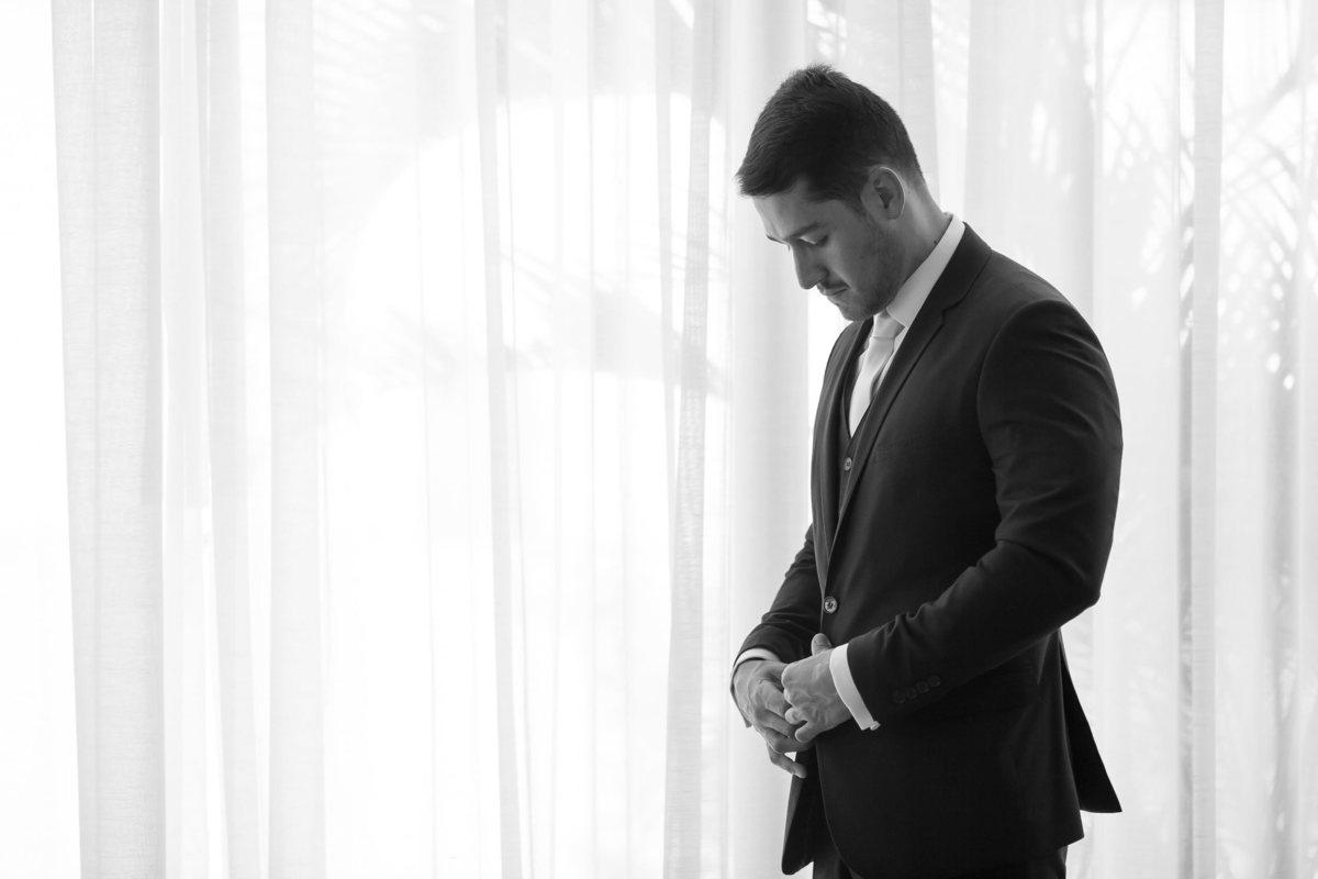 Na frente da janela o noivo Marcos ajeita seu terno, uma foto em preto e branco com uma contra-luz linda.