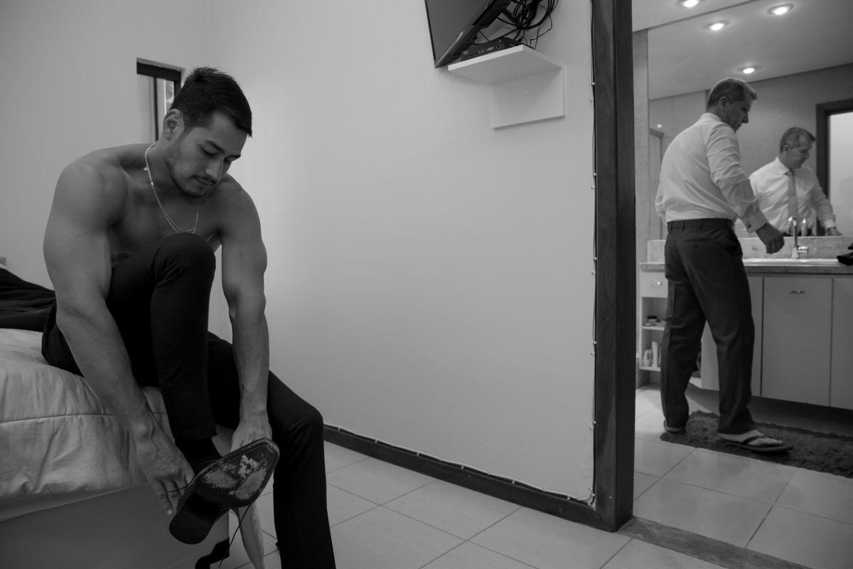 Making of pai e filho, enquanto o noivo coloca o sapato, seu pai se arruma em frente ao espelho do banheiro.