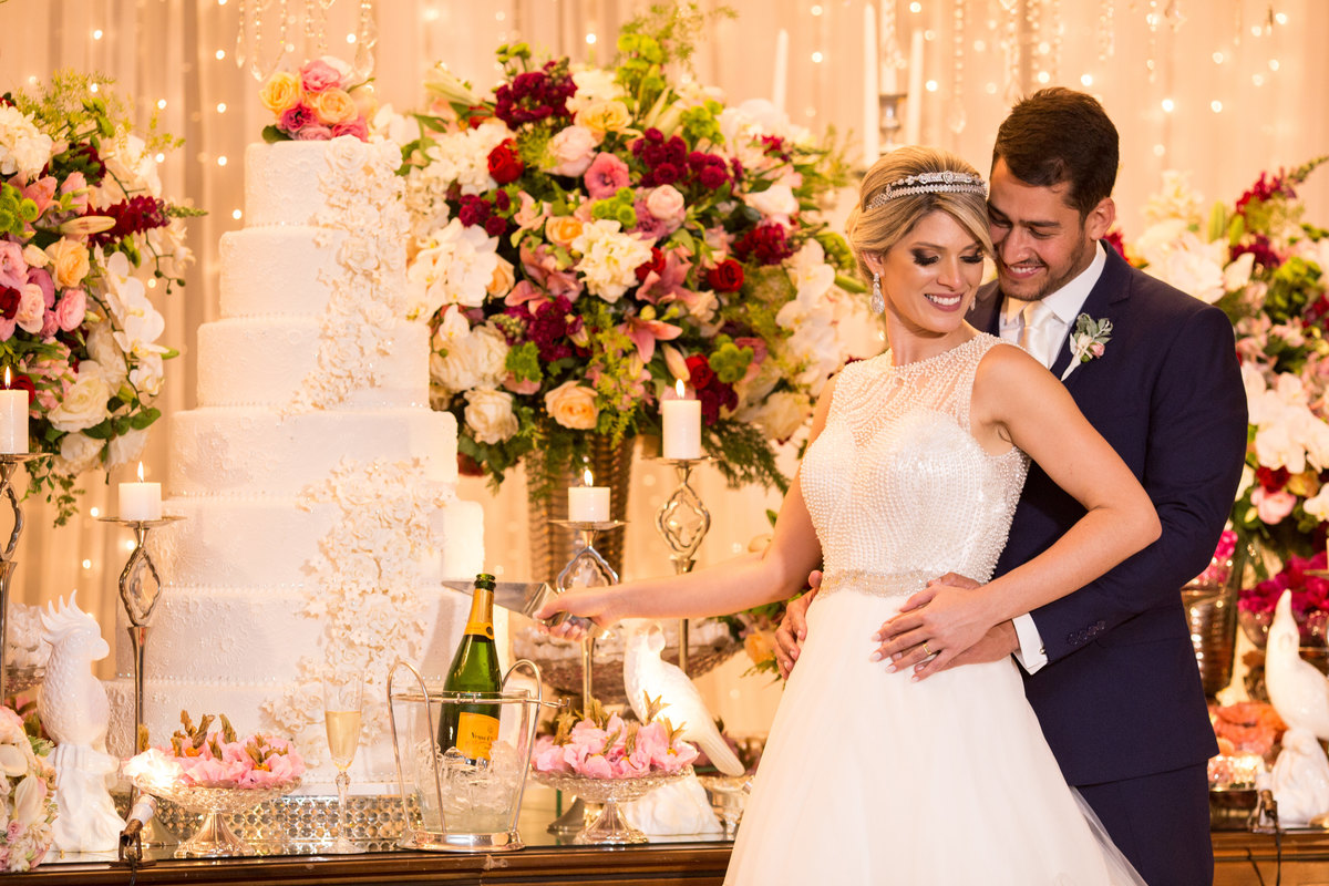 Os noivos fazendo o tradicional corte do bolo, uma linda fotografia com o bolo e toda a decoração da mesa do bolo.