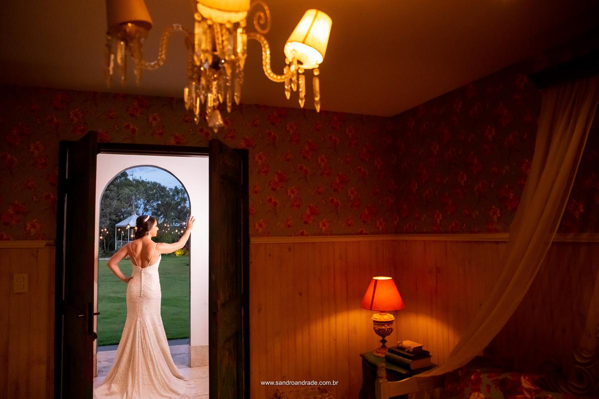 Mostrando as costa do vestido de noiva, Amanda está na frente do quarto da noiva, Amanda admira o céu após o por do sol, ja imaginando como será o por dos sol no gazebo no dia de seu casamento.