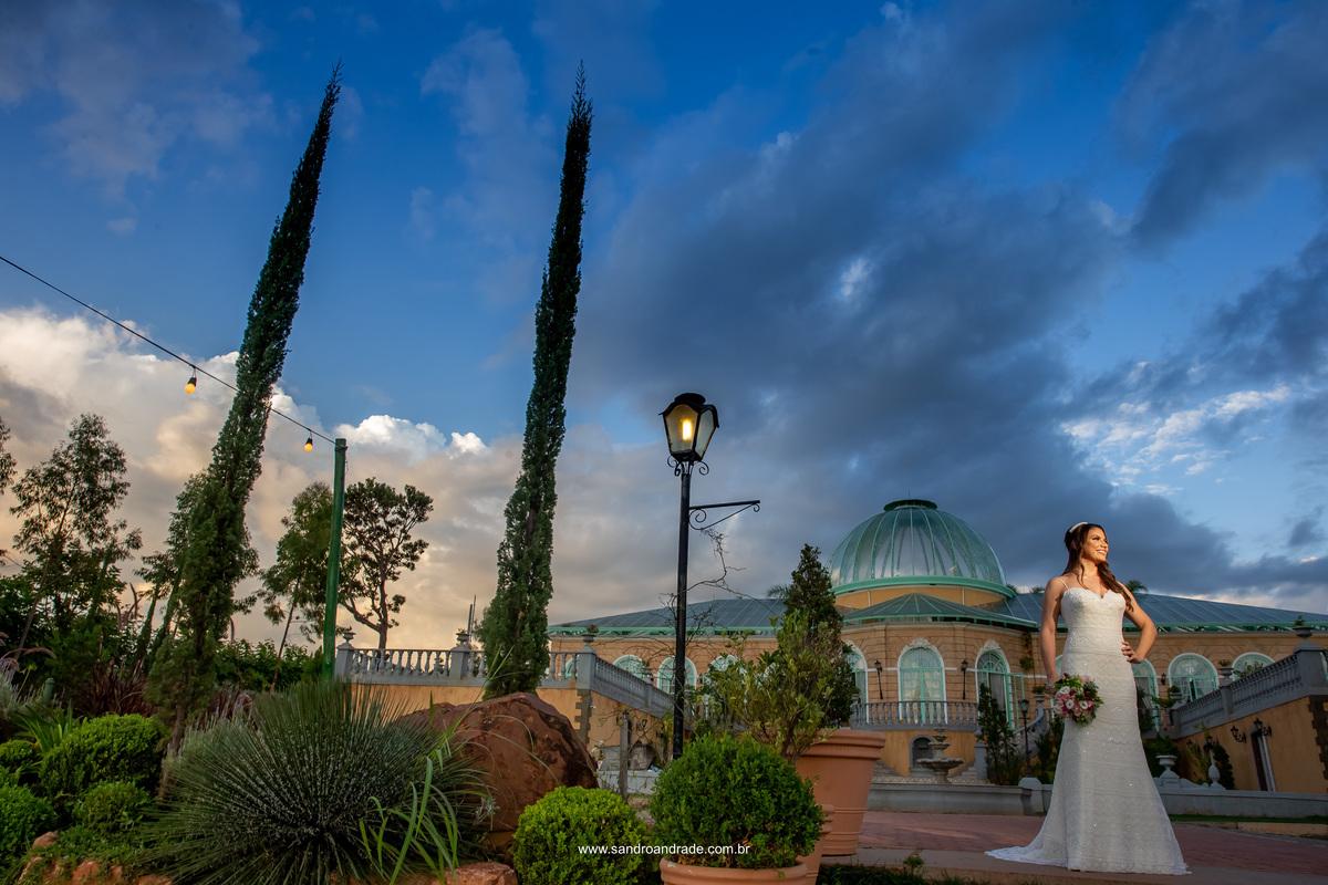 Fotografia minimalista com todo o palazzo da Villa ao fundo e parte do jardim a frente, a noiva está no canto direto, radiante e muito linda.