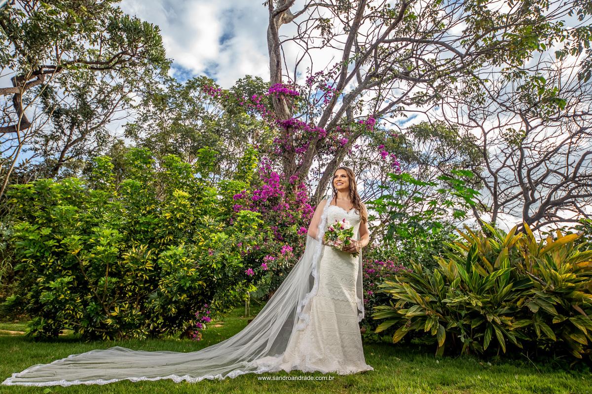 Com seu lindo vestido de noiva e com um véu longo a Amanda posa entre as árvores da Villa com uma linda bouganvíllea roxa de fundo.