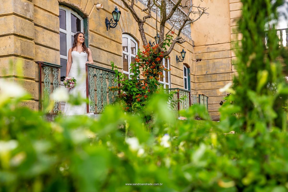 Na varanda do camarim a noiva está encantando com tamanha beleza do local, contraste do amarelo das paredes como verde das folhas.
