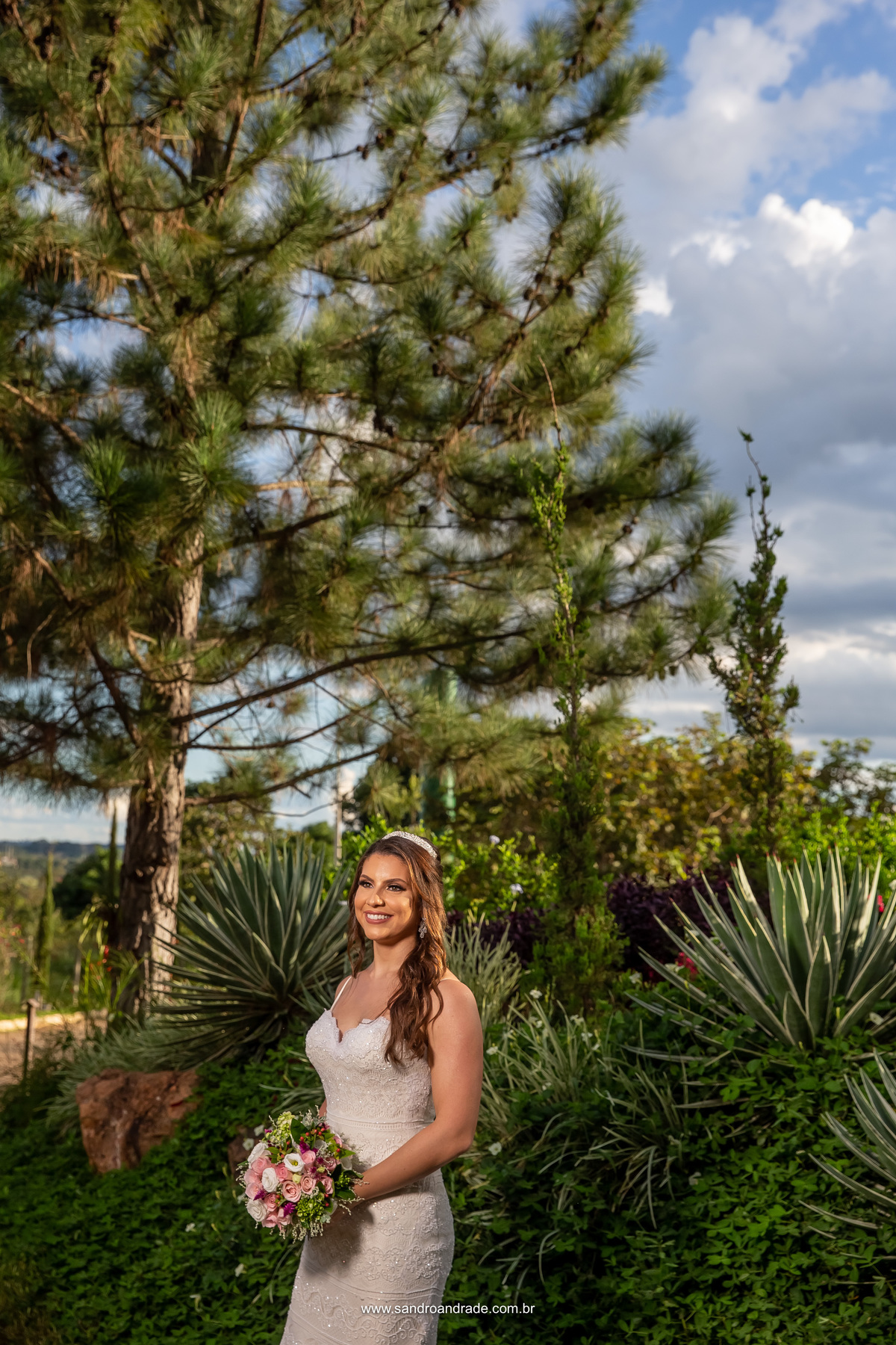 Mais um retrato da noiva, linda fotografia colorida, com uma luz linda de cabelo feita pelo sol, um belíssimo pinheiro ao fundo e um céu azul.