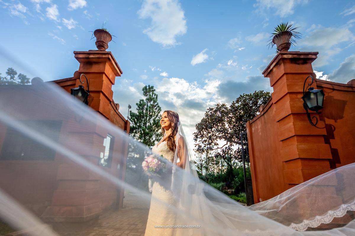 Com uma parte do véu passando na frente da lente, Sandro Andrade fotógrafo de casamentos em Brasilia, fez um lindo click na frente da Villa como muros laranja de moldura para a noiva.