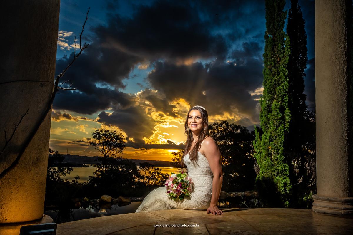 Linda a noiva sentada dentro do gazebo com o buque no colo para esta fotografia linda do por do sol.