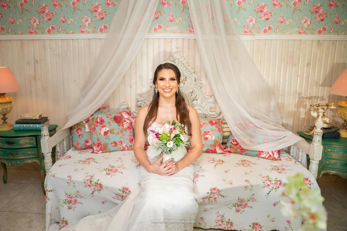Já no quarto da noiva, a Amanda posa com seu lindo buque de noiva e vestindo seu mais belo sorriso.