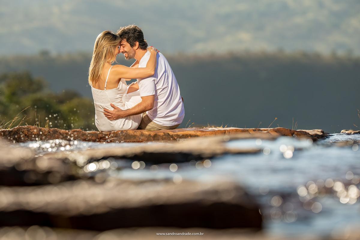 Fotografia linda do casal com o serrado no fundo, muito amor e descontração, com respingos da água da cachoeira.