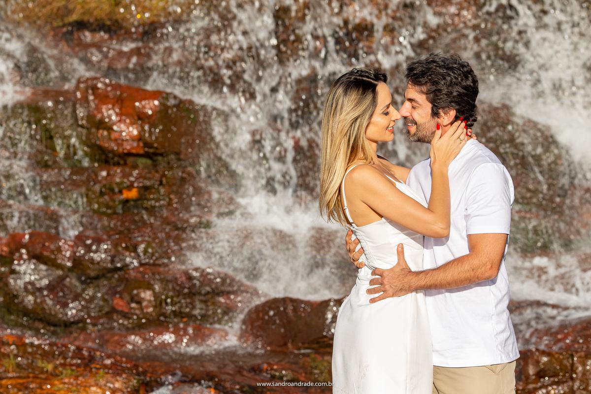 Uma imagem de tirar o fôlego, cachoeira ao fundo, o casal bem juntinho e um quase beijo.