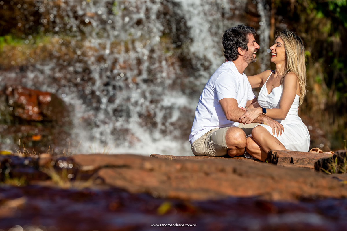 Com muitas gargalhadas eles estão sentado aos pés da cachoeira e rindo vão levando o ensaio com muita leveza.