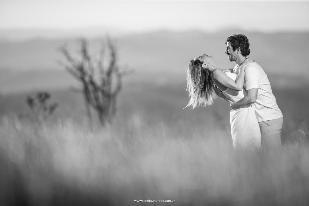 Uma imagem preto e branca para esta galeria tão cheia de cores vibrantes, no meio da grama alta o casal bem agarradinho vão brincando, a fim de conseguir mais uma linda imagem descontraída.