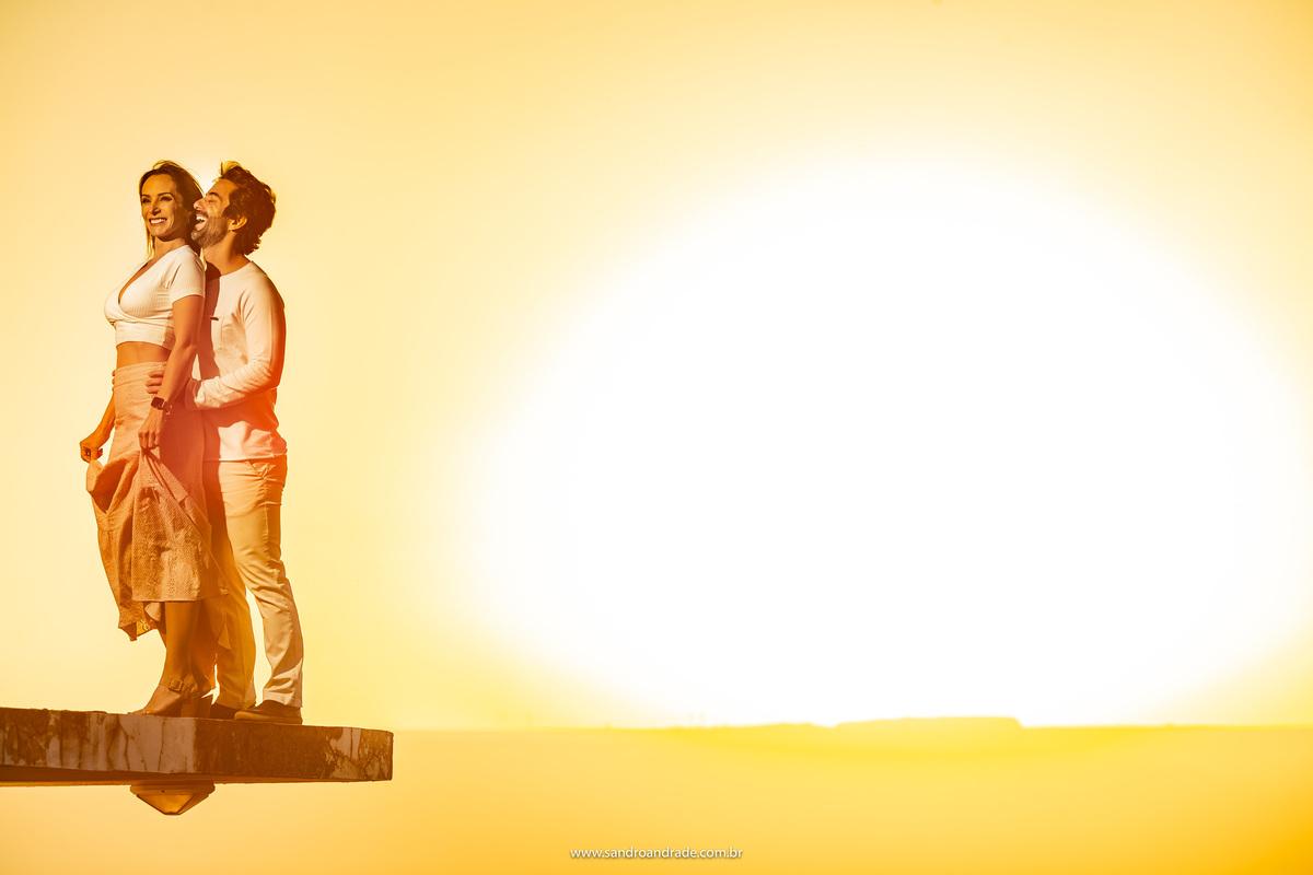 Numa pedaço de laje dando a impressão de estar flutuando, o horizonte com o por do sol, o casal juntinho bem na beiradinha.