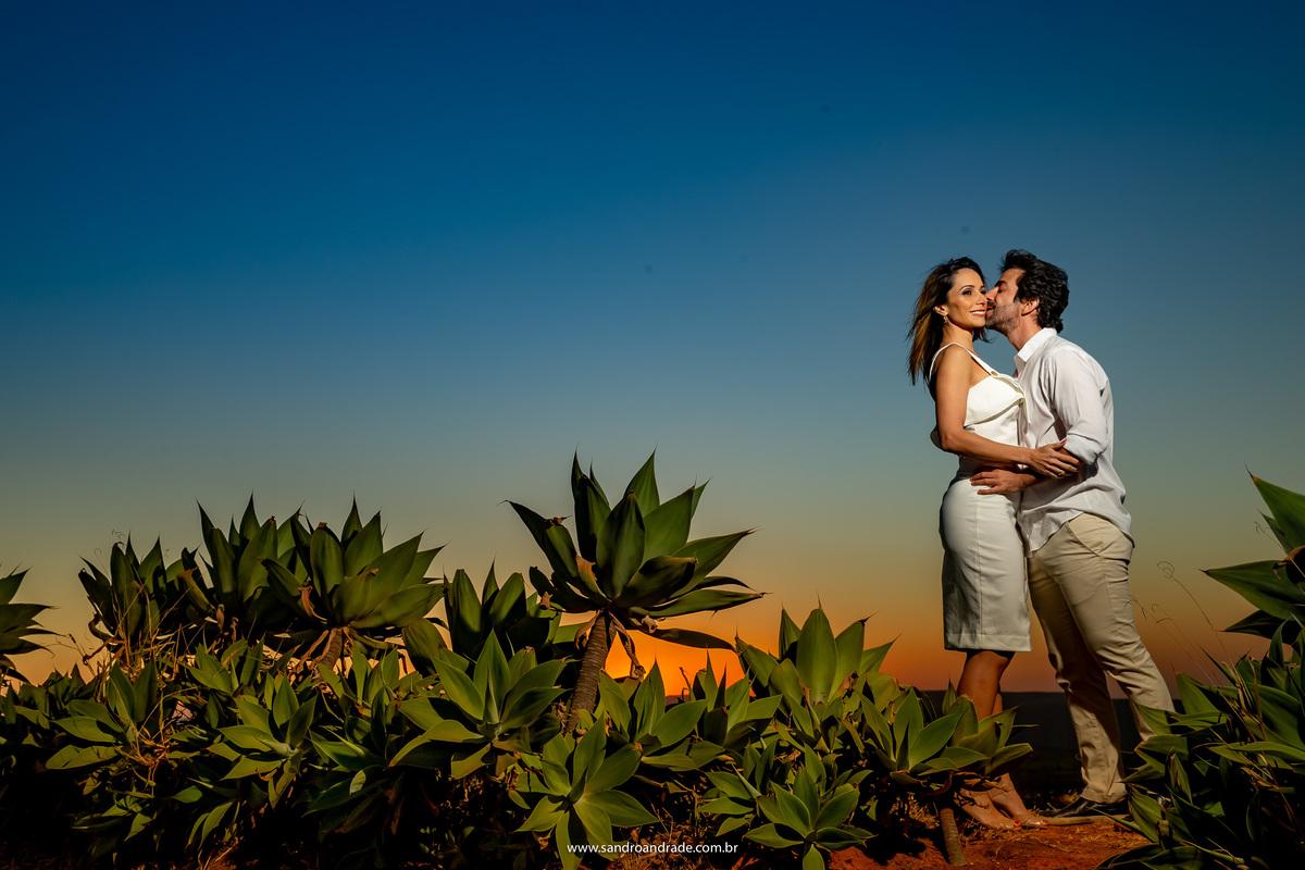 O casal está de frente um para o outro e com um beijo no rosto vamos pegando o finalzinho desse céu contrastado em azul, amarelo e laranja.