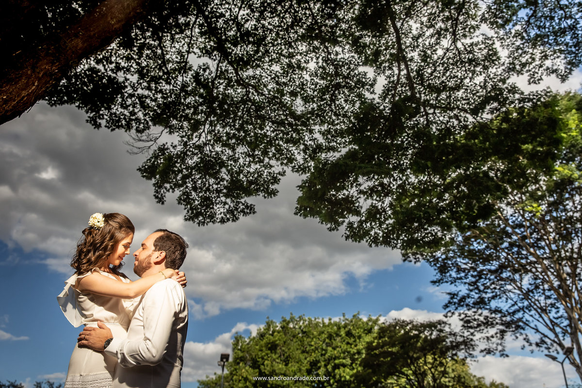 Com uma troca olhar apaixonado, céu azul, nuvens e o verde das arvores. linda fotografia de casal.