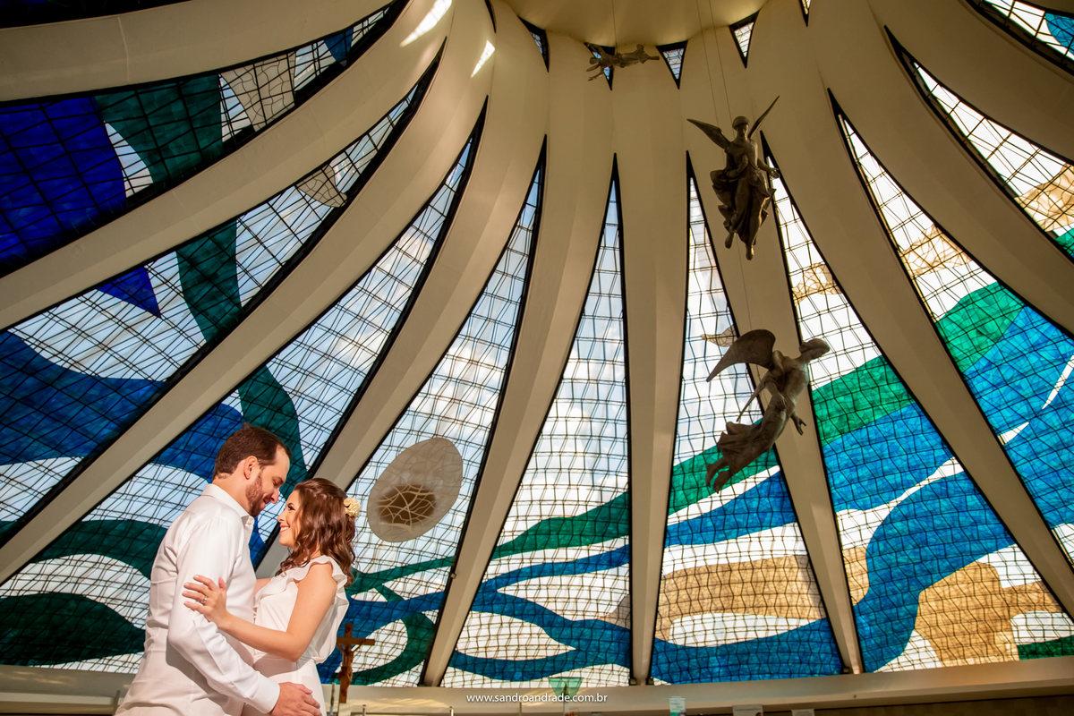 Já na Catedral de Brasília, o casal posa para a foto olhando um para o outro, sorrindo. Para compor esta imagem Sandro usa os vitrais coloridos do teto e os anjos de bronze, linda fotografia.