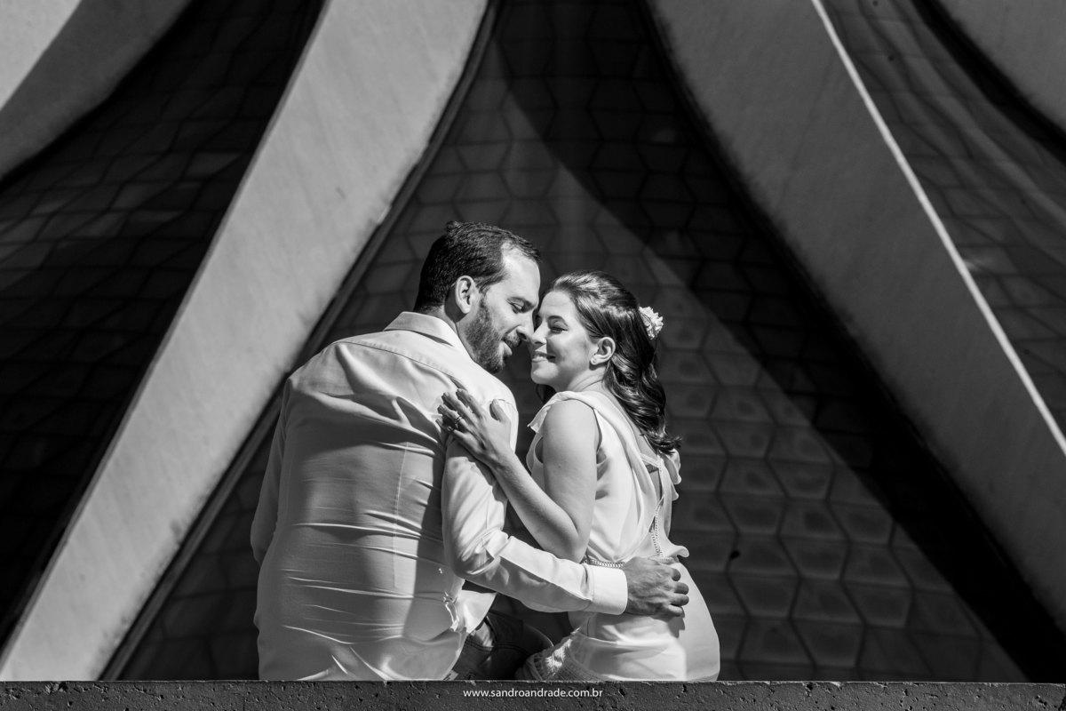 Um dos melhores fotógrafos de casamento em Brasilia, escolhido para registrar o grande dia desse casal, Sandro fez uma imagem PˆB, com o casal bem juntinho, sorrindo e com os olhos fechados, em conjunto com a arquitetura nos detalhes da catedral.
