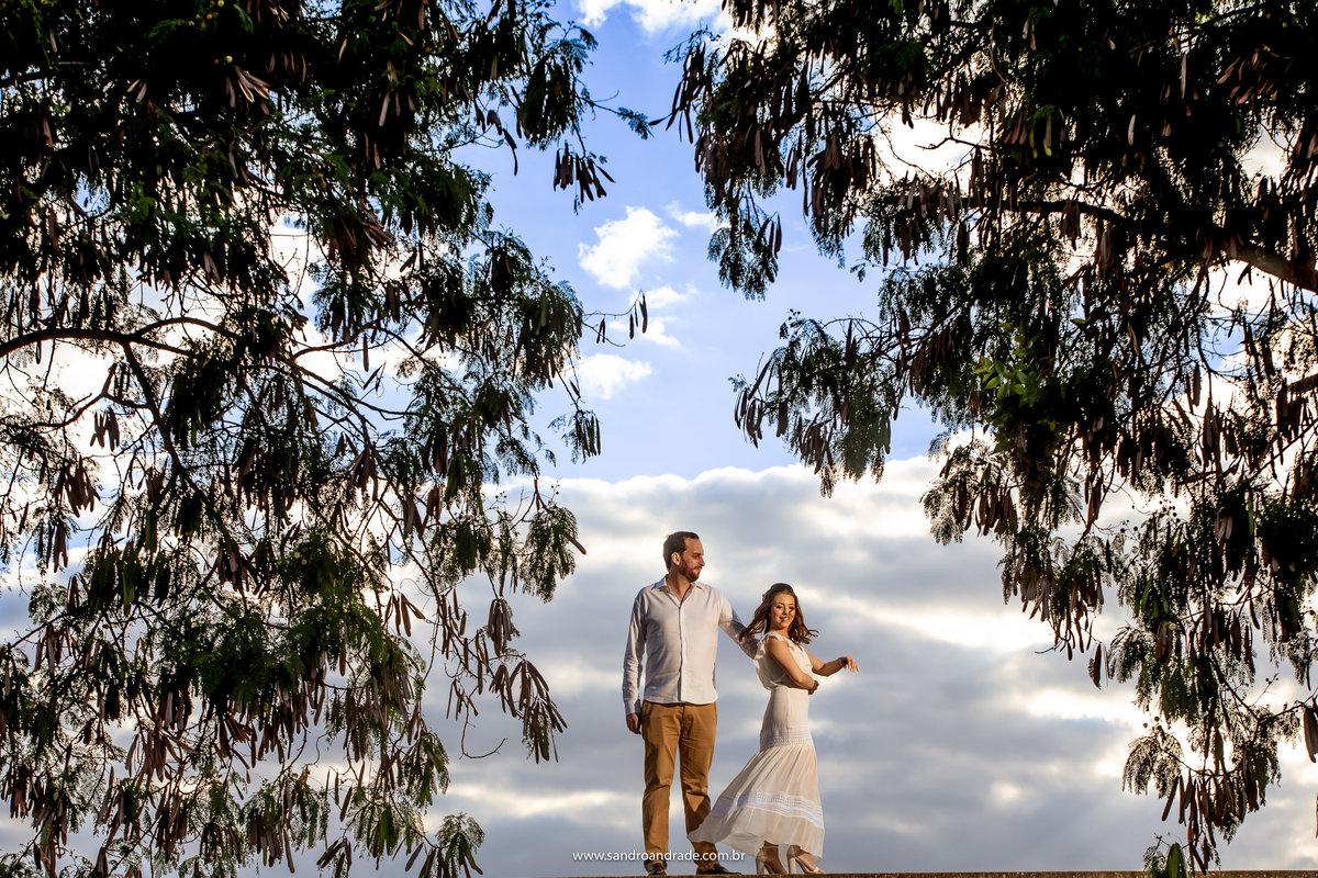 Dançando nas nuvens, é o que parece essa fotografia, os noivos estão dançando e tem folhas nas laterais, mas o fundo, é um lindo céu azul com muitas nuvens.