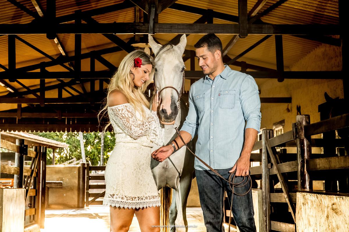 Os dois dando carinho ao cavalo, lindos e apaixonados, ela está com um vestido branco e uma flor de hibisco no seu lindo cabelo loiro.