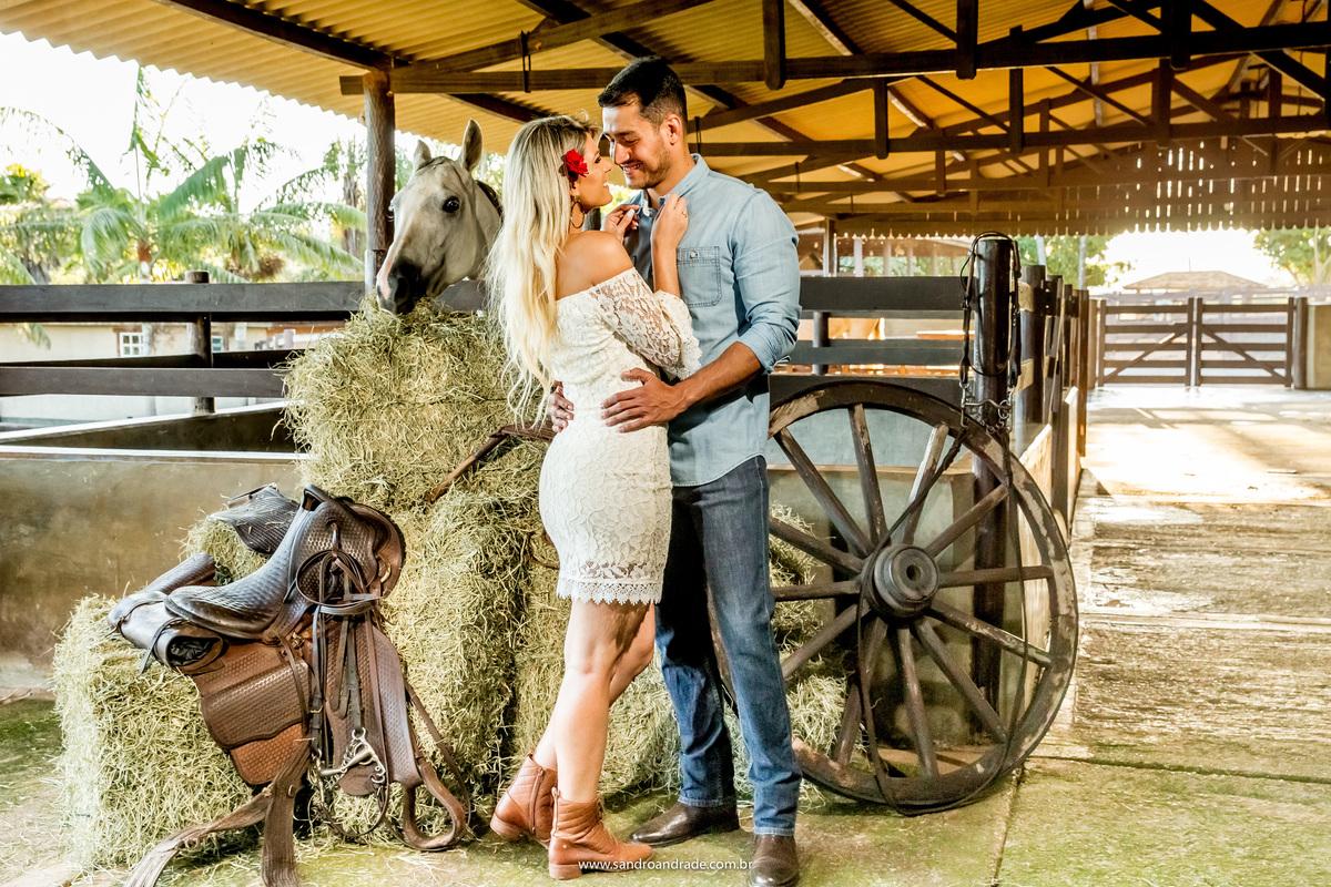 Em meio ao feno, cavalo e baias e uma roda de carroça, eles se abraçam e se olham com muito amor.