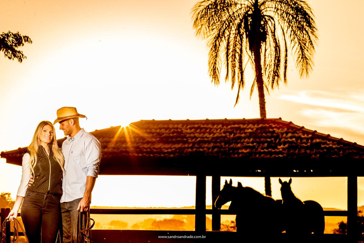 Uma linda foto do por do sol, cm três cavalos em silhueta ao fundo, abraçados, ele apaixonado olha para sua amada cm seu chapéu de cowboy.