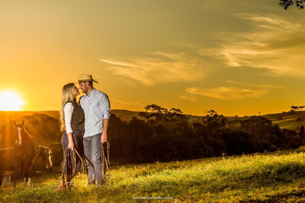 Céu amarelinho, por do sol, muita grama e cavalos, abraçados de frente um para outro eles fazem juras de amor.