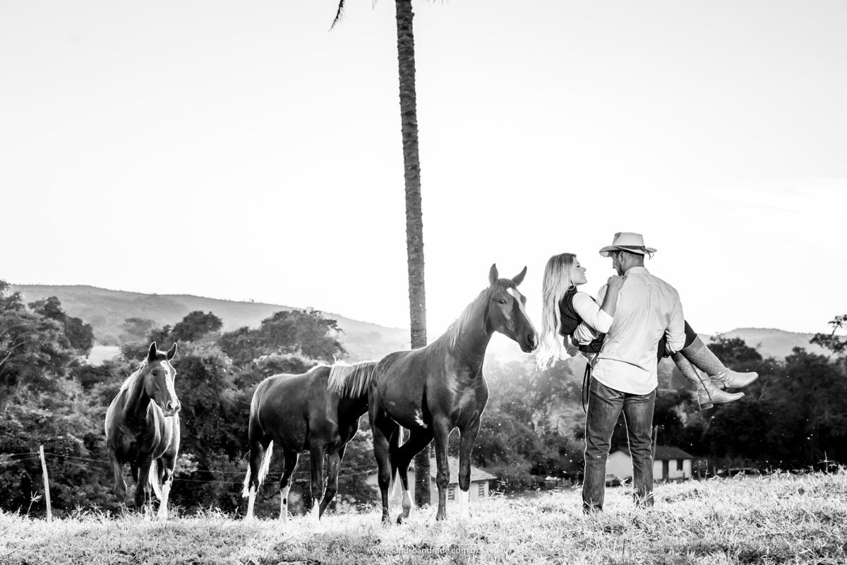 Ainda com sua amada no colo, eles se olham e um dos cavalos cheira o cabelo da noiva, uma fotografia PeB.