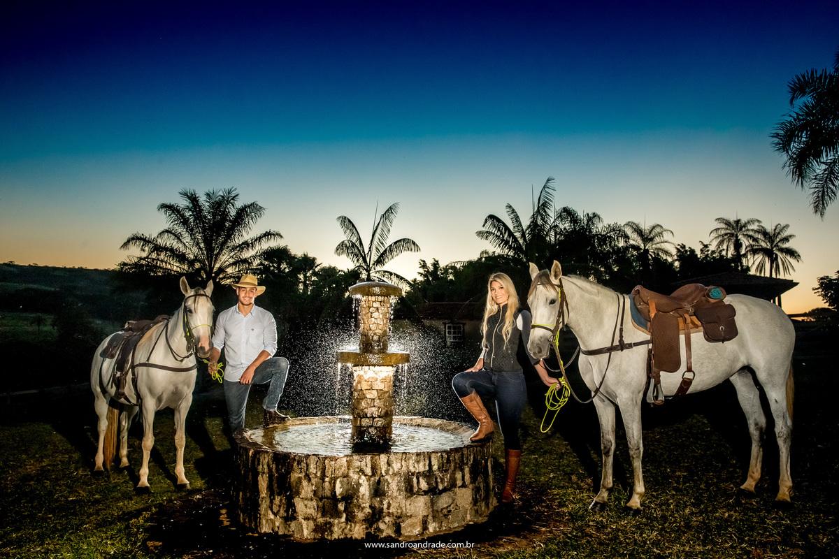 Uma fotografia básica com um céu azul e os noivos olhando para a foto e parados na frente da fonte para os cavalos descansarem.