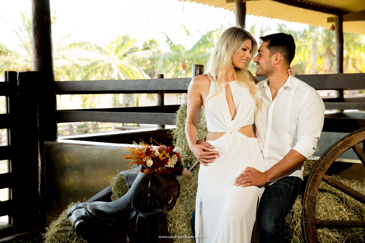 Apaixonados...a noiva sentada no colo do noivo, numa das baias de cavalo sentados no feno.