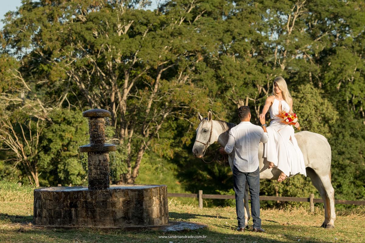 Perto da fonte de água dos cavalos, o noivo da a mão a sua noiva, linda vestida de branco, parecendo uma amazona sentada em um lindo cavalo branco.