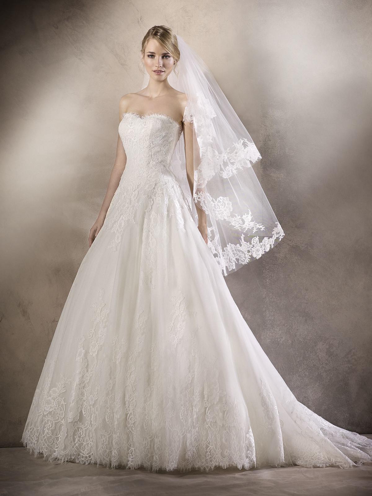 Requintado vestido de noiva estilo princesa em tule, com decote em coração. A renda decora o decote e todo o vestido, conferindo um ar muito romântico, rematado por umas costas com elegantes botões.