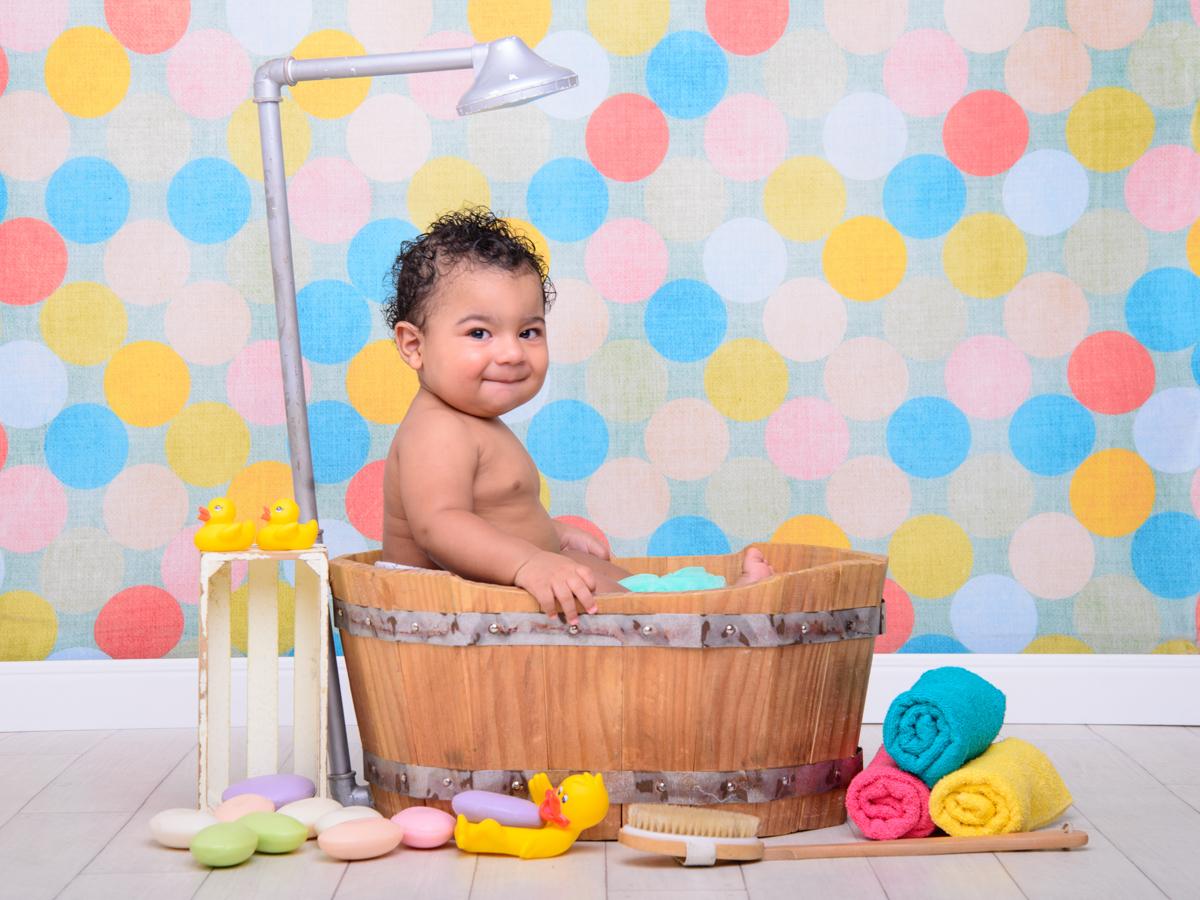 sessão de banho, toalha, sabonete, banheira, chuveiro, sabão, espuma, parede colorida, cabelo cacheado, patinhos.