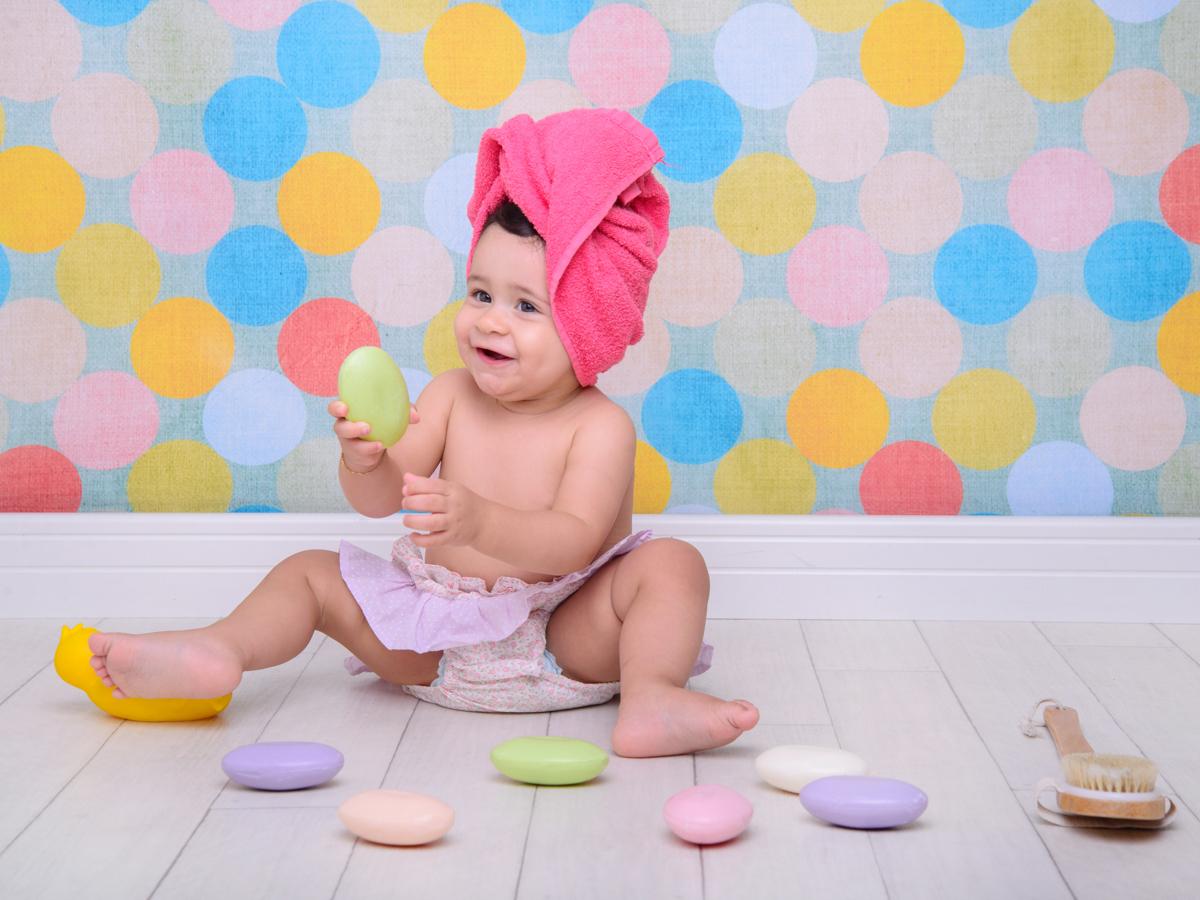 sessão de banho, toalha, sabonete, parede colorida, escova, brincadeiras, covinhas.