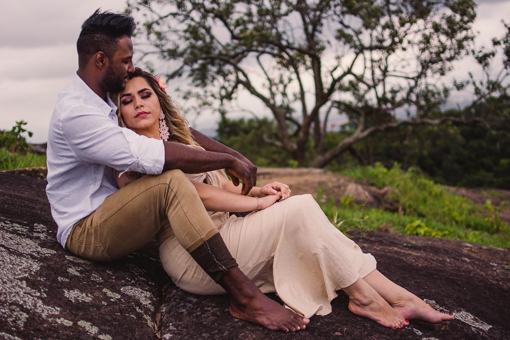 fotografia do casal sentado na pedra. Ensaio pré casamento realizado no Parque da Fonte Grande, Vitória - ES.