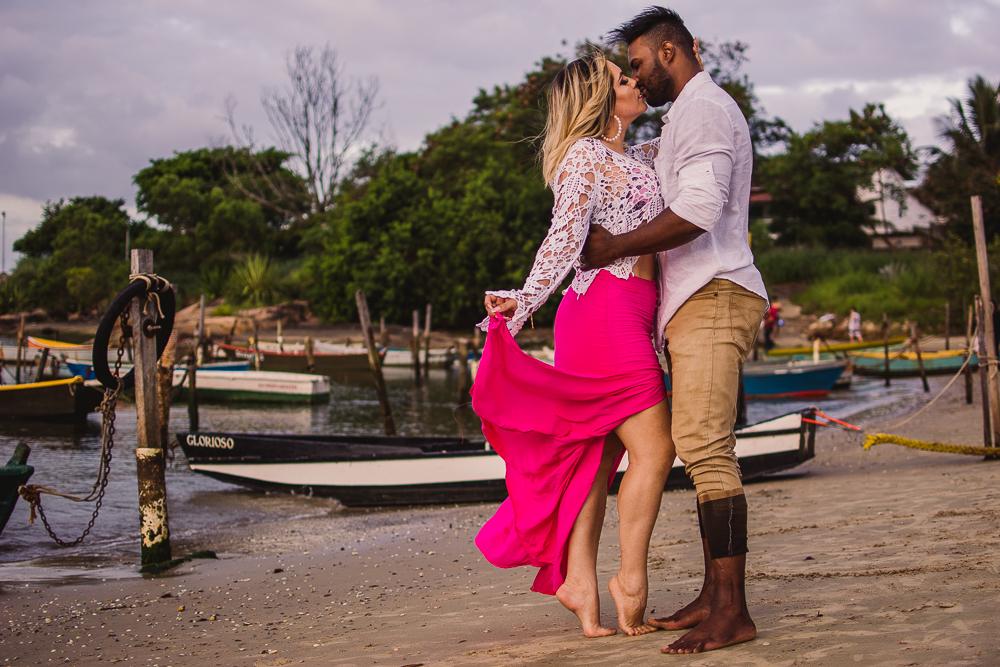 Fotografia de casal na praia da Ilha do Frade. Noiva segurando saia. Casal se beijando.