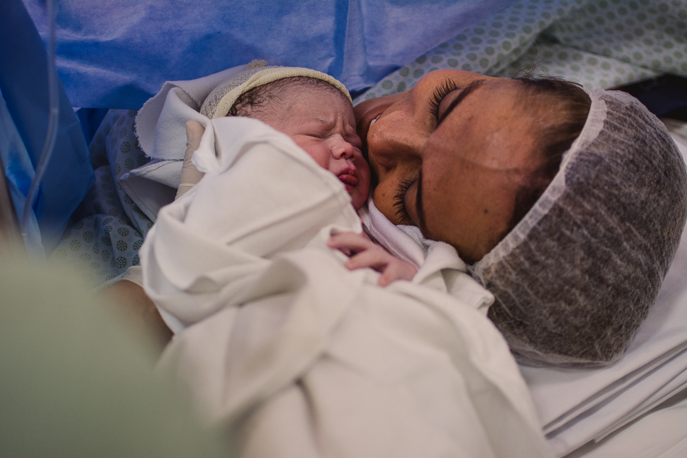 Fotografia documental de parto. Bebê encostando rostinho na mãe.
