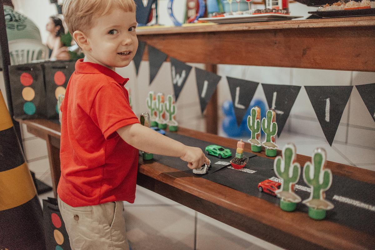 Fotografia do aniversariante brincando com os carrinhos na mesa da decoração.