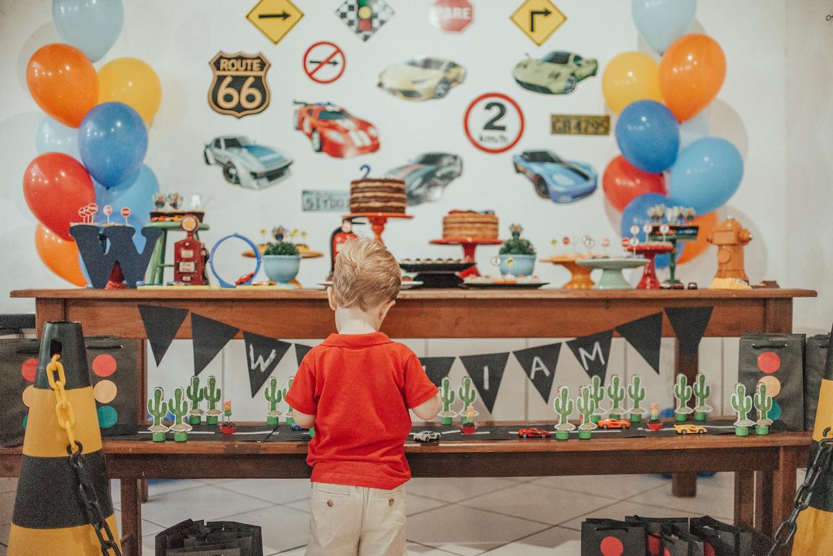 Retrato da mesa de decoração com o aniversariante brincando com os carrinhos da decoração. Tema da festa: Hotwheels.
