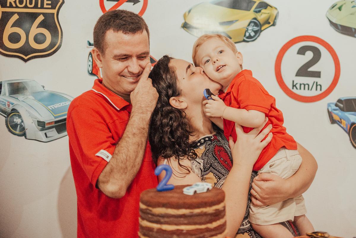 Fotografia dos pais com filho na mesa de decoração. Mãe beijando o filho no rosto. Tema da festa Hotwheels.