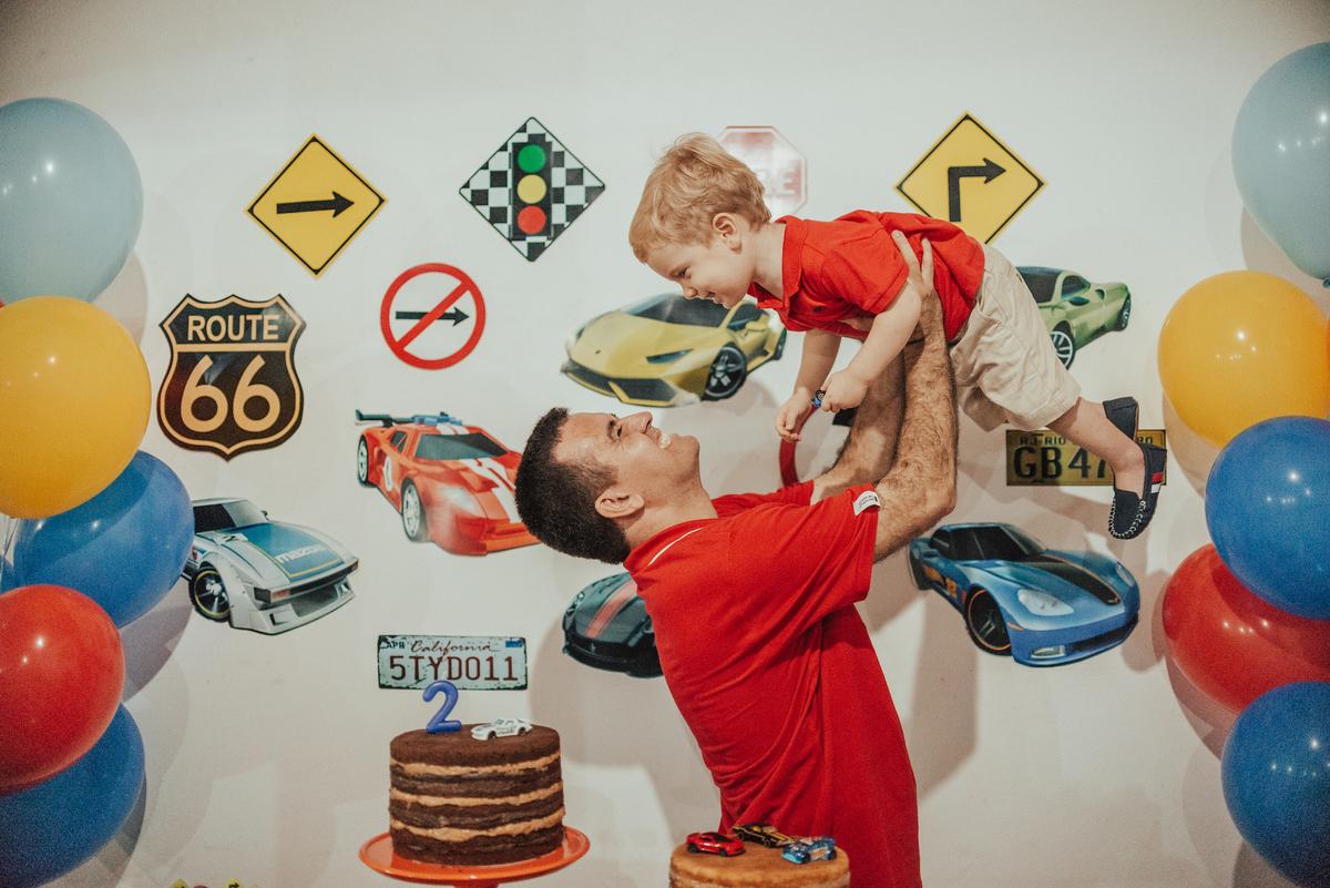 Fotografia de festa de aniversário de 2 anos. Pai brincando com o filho.
