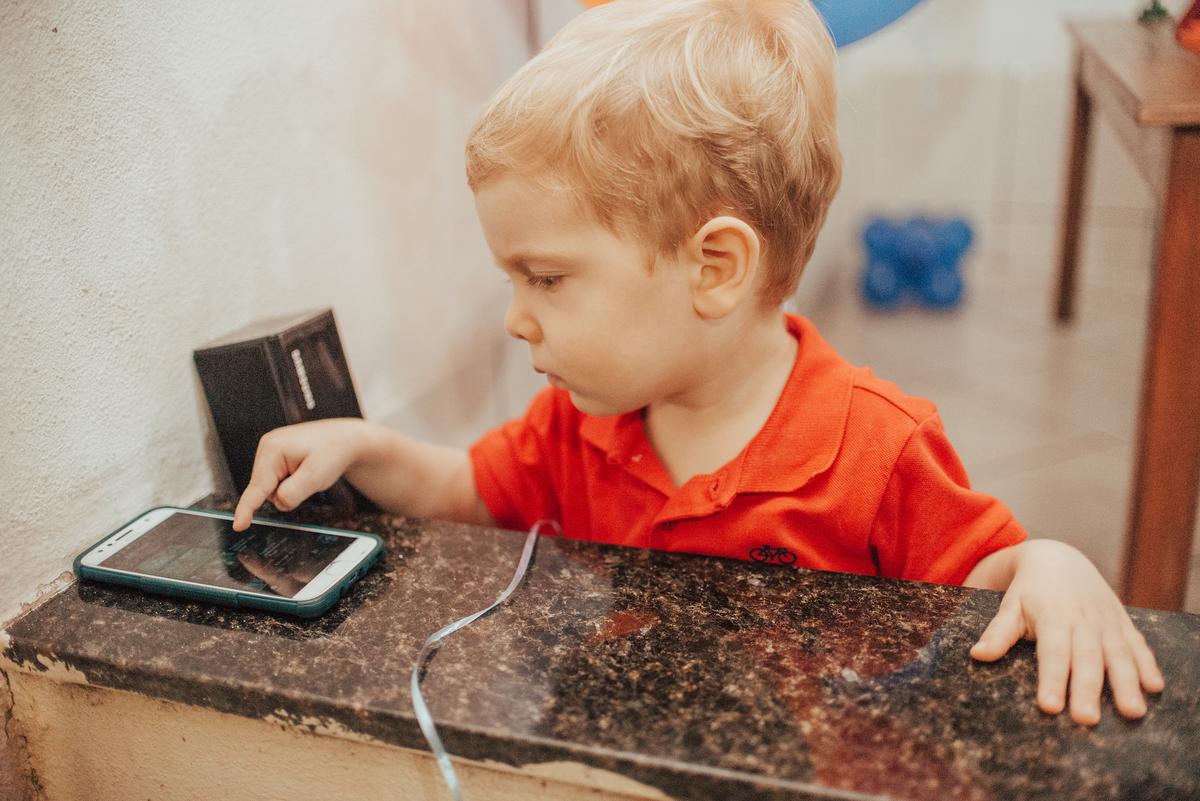 Fotografia do aniversariante escolhendo as músicas a serem tocadas no seu aniversário de 2 anos.