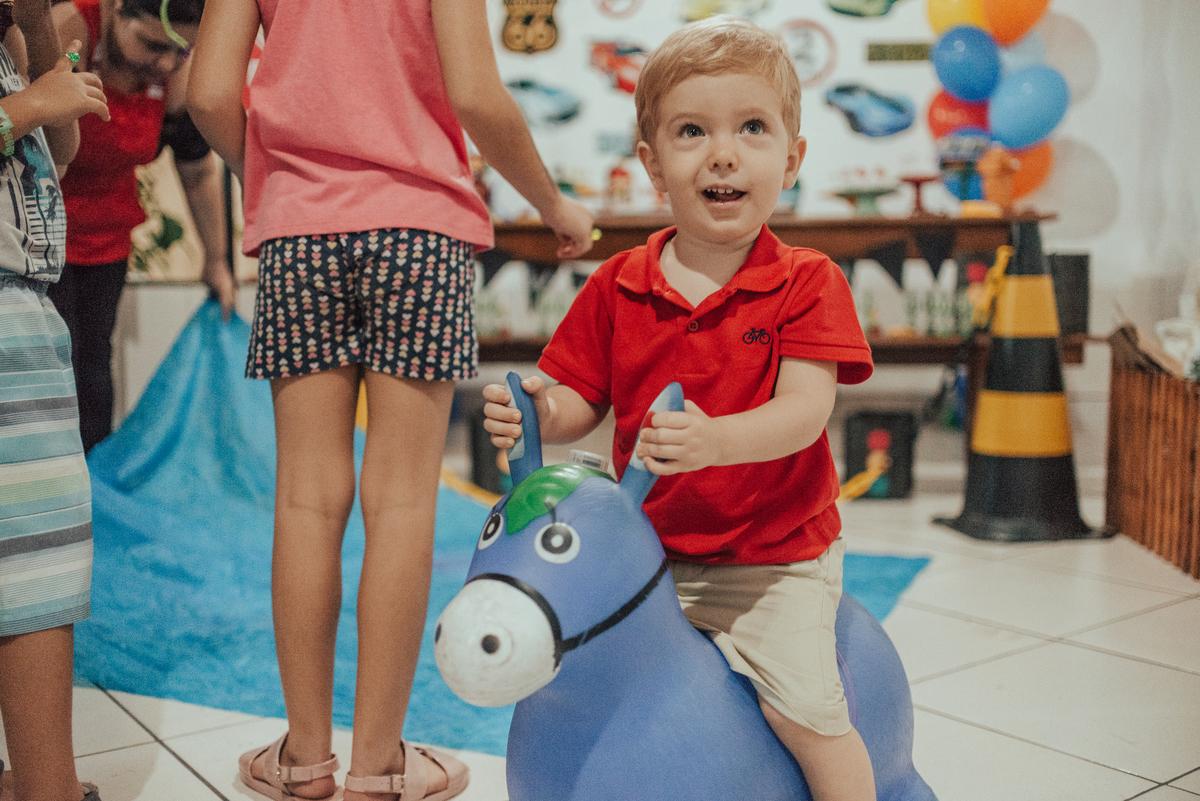 fotografia do aniversariante brincando com seu cavalinho pula pula.