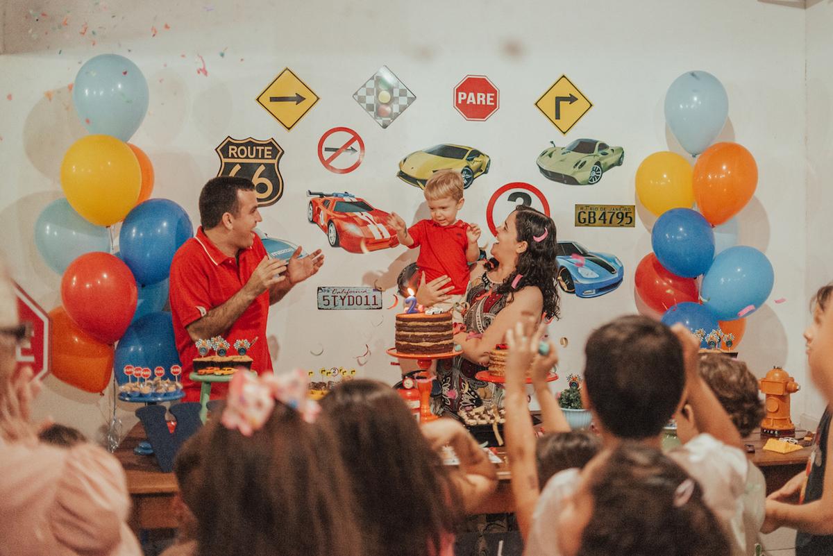 Fotografia da família e amigos cantando parabéns na festa de aniversário de 2 anos. Tema Hotwheels.