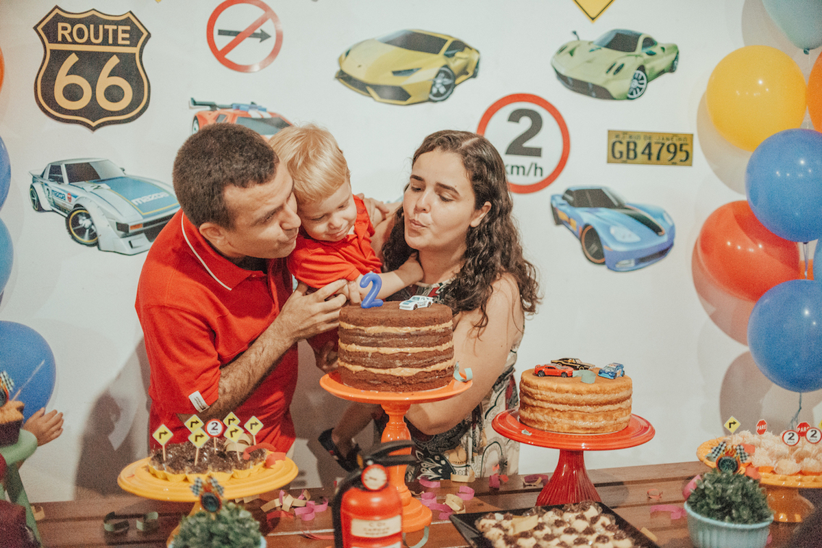 Fotografia, assoprando bolo de aniversário da festa tema Hotwheels.