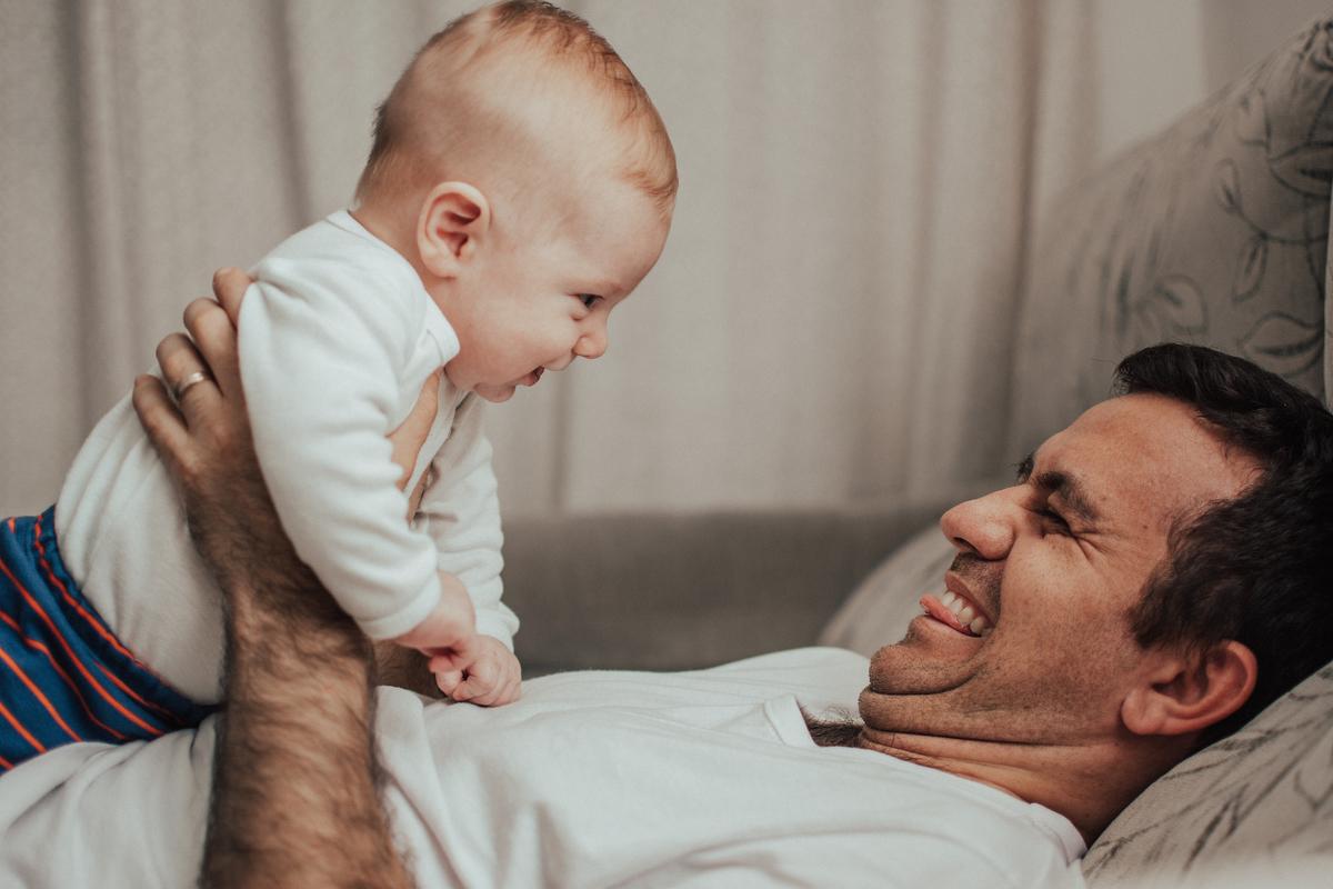 Papai segurando bebê e sorrindo para ele. Fotografia Documental de Família.