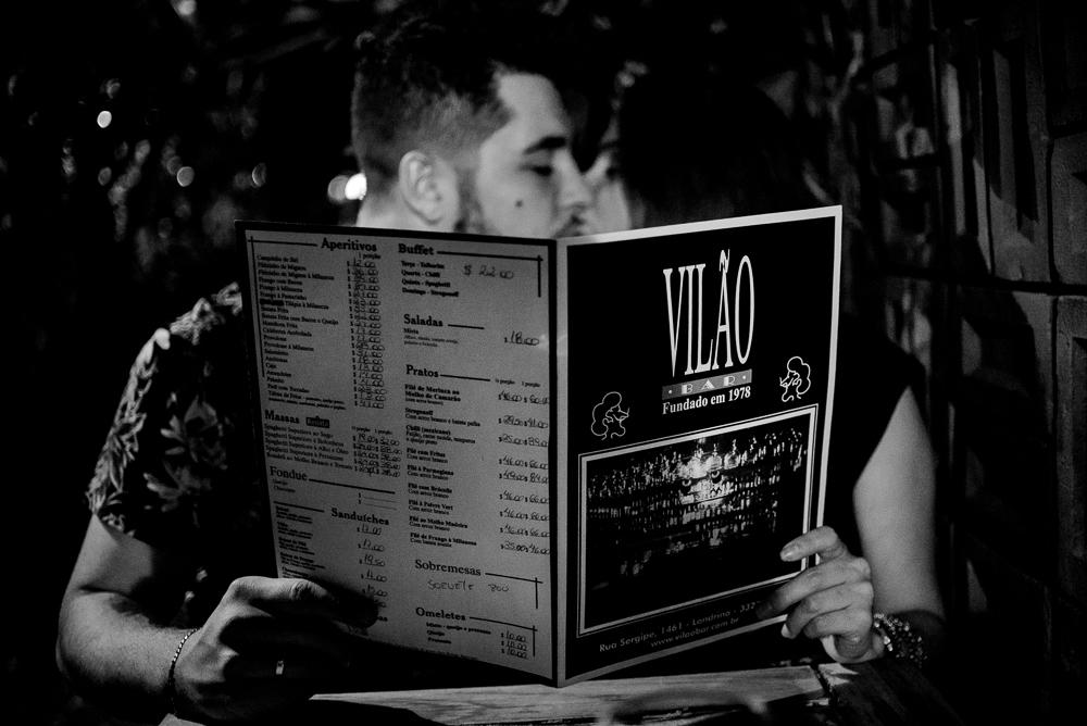 Casal segurando cardápio do Vilão Bar. Ensaio Pré Casamento, externo a noite, realizado em Londrina, Paraná. Ensaio no Vilão Bar.