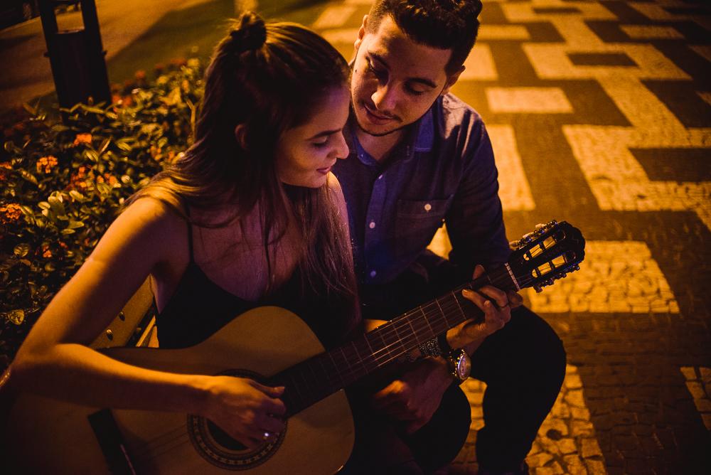 Fotografia pré casamento. Foto do casal tocando violão na praça em Londrina - PR.