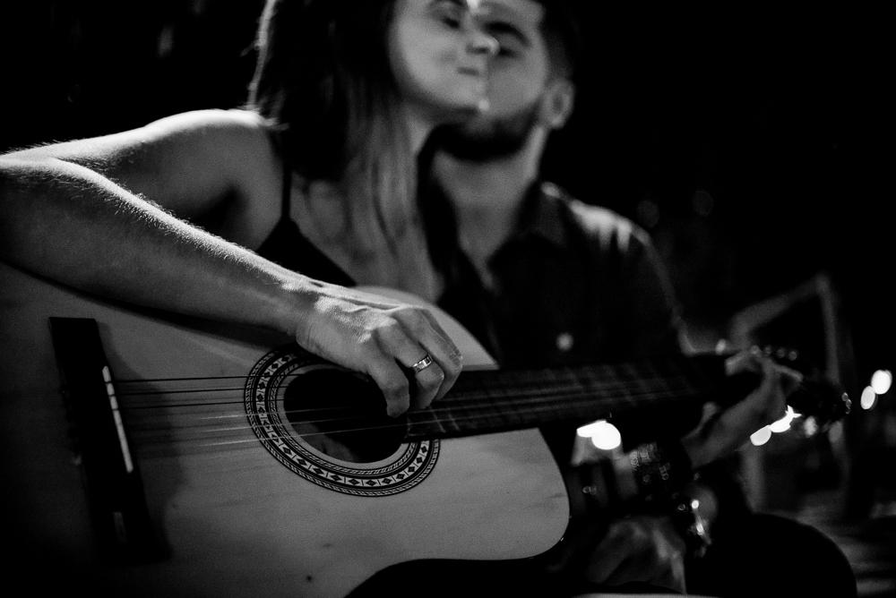 Fotografia preto e branco. Ensaio pré casamento do casal em Londrina. Noiva tocando violão para o noivo.