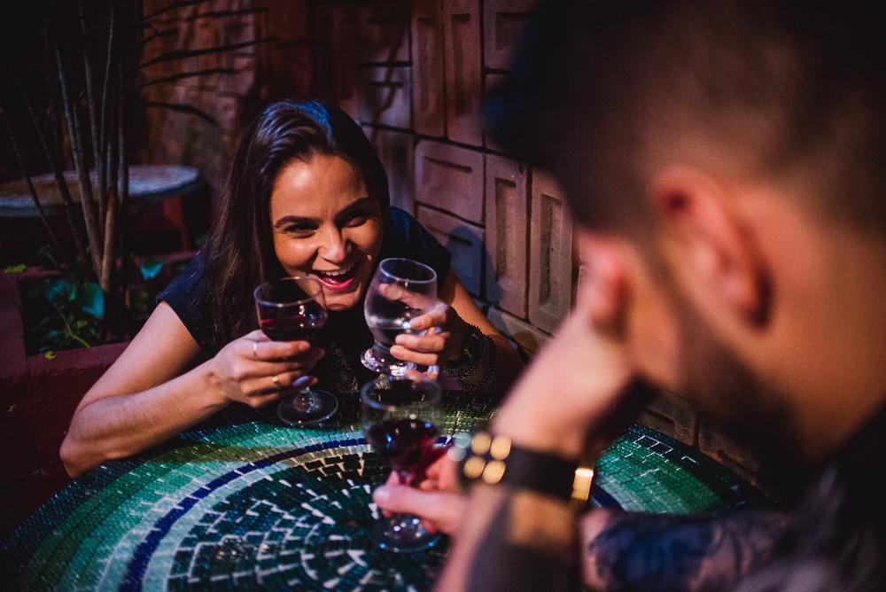 Fotografia de ensaio pré casamento realizado no Vilão Bar. Noiva gargalhando para noivo. Bebendo vinho.